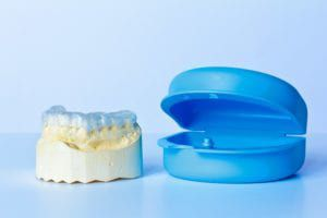Night guard on a mold of a mouth next to a blue plastic case