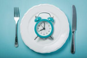 A blue alarm clock sitting atop a plate with a knife and a fork all on a blue background