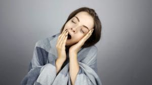 Drowsy woman wrapped in a blanket and yawning