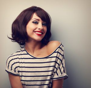 Woman in striped shirt smiling against a gray wall