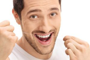 Smiling man having a good time while easily flossing his teeth