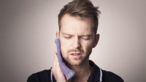 Man holding face in pain