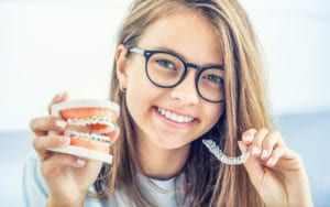 Woman holding braces and invisalign